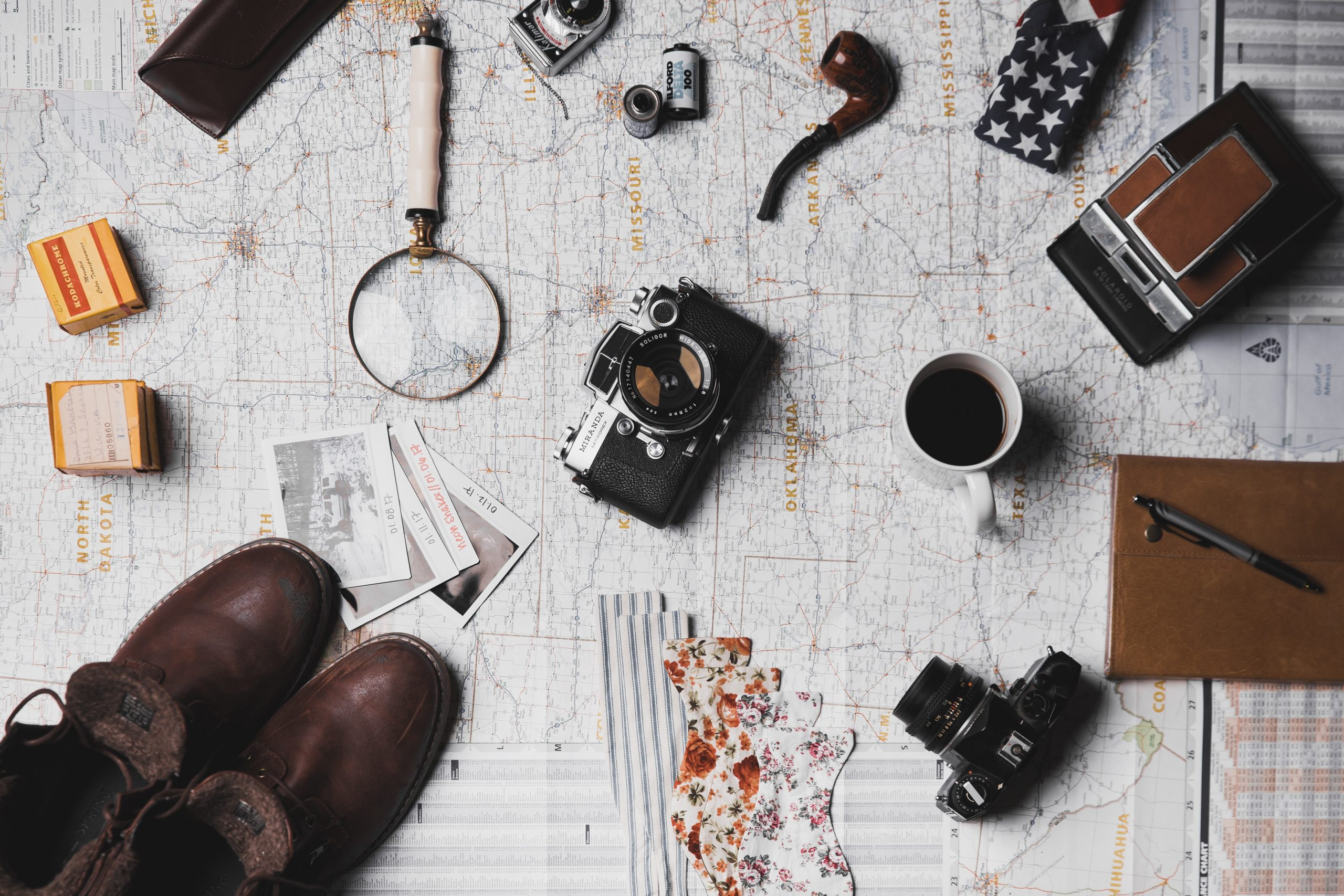 A camera, pair of brown boots, white ceramic mug, gray and black pens magnifying glass, and photographs all on top of a map.